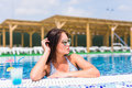 Tenned beautiful woman in blue bikini and sunlasses sitting in swimming pool with cocktail. Fashionable portrait. Royalty Free Stock Photo