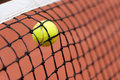 Tennis ball bouncing on the net at a clay court Royalty Free Stock Photo