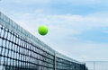 Tennis ball flying over middle net court on background blue sky Royalty Free Stock Photo