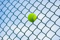 Tennis ball on metal wire against sky. Concept of tennis protection equipment Royalty Free Stock Photo