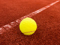 Tennis ball near base line on clay court you can use it to show out or in Stock Photo