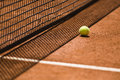 Tennis ball and net on a clay court next to the shot with shallow depth of field Royalty Free Stock Images