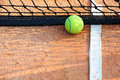 Tennis ball and net on a tennis clay court Royalty Free Stock Image
