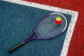 Tennis ball racket colored and placed in the corner of a synthetic field Royalty Free Stock Image