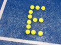 Tennis ball in shape of letter E on a blue artificial grass court Royalty Free Stock Photo
