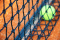 Tennis ball on a tennis clay court focus net Stock Image