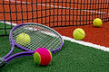 Tennis balls racket ball and arranged around the net on a synthetic field Stock Image