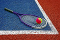 Tennis balls racket colored ball and placed in the corner of a synthetic field Royalty Free Stock Images