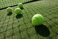 Tennis balls on tennis grass court. Royalty Free Stock Photo