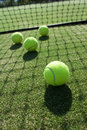 Tennis balls on tennis grass court. Royalty Free Stock Photo