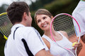 Tennis couple at the court looking happy and smiling Stock Image