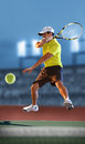 Tennis player in action inside court at night Royalty Free Stock Image