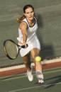 Tennis player reaching to hit ball female the on court Stock Photography