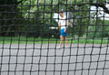 Tennis player seen through the net Royalty Free Stock Image
