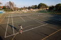 Tennis practice coach pupil courts late afternoon with school s for junior males player at hca school outside durban south africa Royalty Free Stock Images