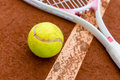 Tennis racket with a ball lying on the floor of clay court Royalty Free Stock Photography