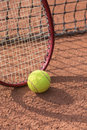 Tennis racket and balls on the clay court close up view of Royalty Free Stock Photos
