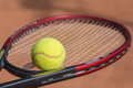 Tennis racket and balls on the clay court close up view of Royalty Free Stock Images