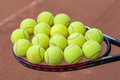 Tennis racket and balls on the clay court close up view of Royalty Free Stock Image