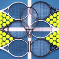 Tennis rackets with balls on hard surface court.