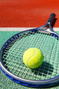 Tennis racquet and ball on the clay tennis court close up of Stock Image