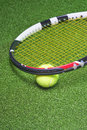 Tennis racquet with ball over green artificial grass vertical image Royalty Free Stock Photos