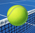 Tennis sport concept with a ball flying over the court net or netting as a leisure fitness and exercise symbol and health care Royalty Free Stock Images