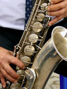 Tenor saxophone fragment of with hands of musician Stock Photos