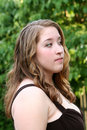 Tense prom girl closeup profile of a teenage in a brown gown looking away to her left with a expression taken outdoors Stock Photography