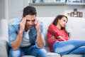 Tensed man after argument with woman men women while sitting on sofa Stock Photography