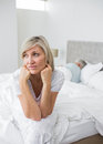 Tensed mature woman sitting in bed with man in background closeup of a women men at home Stock Photography