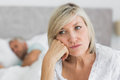 Tensed mature woman sitting in bed with man in background closeup of a women men at home Royalty Free Stock Photos