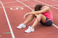 Tensed sporty woman sitting on the running track full length of a Royalty Free Stock Photography