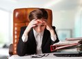 Tensed young business woman holding her head while at work Royalty Free Stock Image