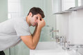 Tensed young man at washbasin in bathroom side view of a Royalty Free Stock Photography