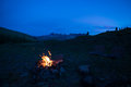 Tent and burning camp fire at dusk on the mountains. Summer adventures and exploration in the Alps. Selective focus on fire, color