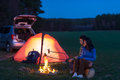Tent camping car couple sitting by bonfire Royalty Free Stock Images