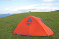 Tent the orange in green mountain meadow Royalty Free Stock Images