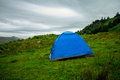 Tent pitched on a green hillside blue against gloomy sky Stock Images