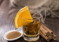 Tequila gold with cinnamon on wooden background Royalty Free Stock Images
