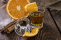 Tequila shots with cinnamon and orange on wooden background Royalty Free Stock Image