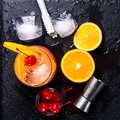 Tequila Sunrise cocktail, orange, ice cubes, maraschino cherries, ice tongs and jigger on a wet black slate tray. Cocktail Set. To Royalty Free Stock Photo