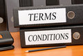 Terms and conditions text in uppercase black letters on two white labels attached to two binders placed on a wooden office desk Royalty Free Stock Photo