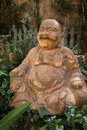 Terracotta buddha statue of a seated smiling with a jovial expression in greenery at the foot of a tree Stock Photography