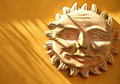 Terracotta smiling sun on a wall plaque of the face of the ringed with rays colourful orange painted Stock Photography