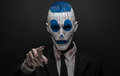 Terrible clown and Halloween theme: Crazy blue clown in black suit isolated on a dark background in the studio Royalty Free Stock Photo