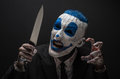 Terrible clown and Halloween theme: Crazy blue clown in a black suit with a knife in his hand isolated on a dark background in the Royalty Free Stock Photo