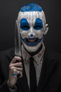 Terrible clown and halloween theme crazy blue clown in a black suit with a knife in his hand isolated on a dark background in the Stock Photography