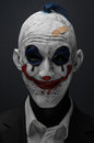 Terrible clown and Halloween theme: Crazy terrible blue clown in black suit isolated on a dark background in the studio