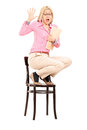 Terrified woman standing on a chair isolated on white background scared Royalty Free Stock Photos